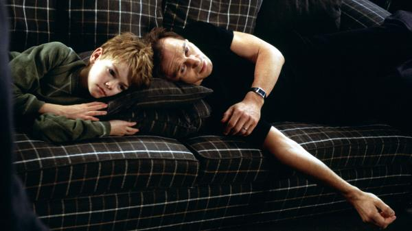 Sam (Thomas Brodie-Sangster) and his stepfather Daniel watch the movie <em>Titanic</em> to try to cure their love woes.