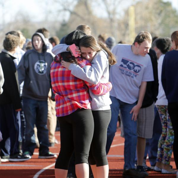 Students comfort each other at Arapahoe High School on Friday.