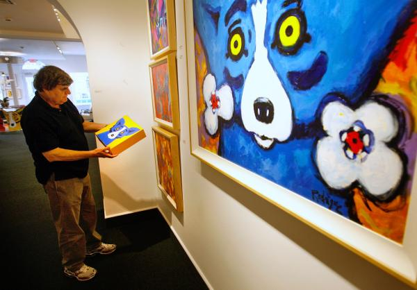 "Artist George Rodrigue looks at one painting of the three-canvas series titled ""Three Coins in the Fountain"" in 2010."