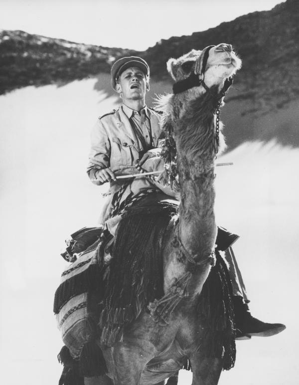 "Peter O'Toole rides across the desert in Jordan during the filming of <em>Lawrence of Arabia </em>in November 1961. He says that at first, learning to ride a camel was ""impossible."""