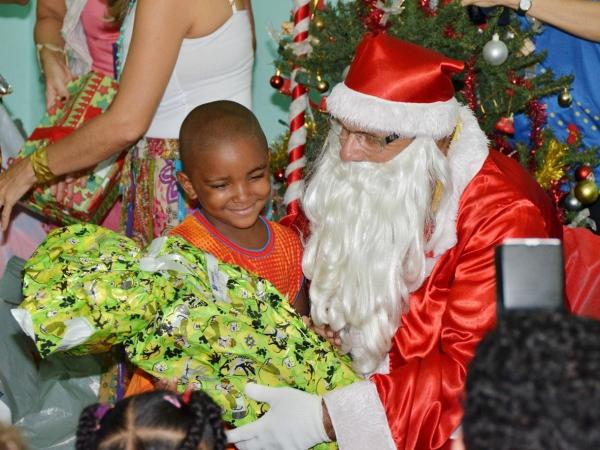 A man dressed as Santa Claus, representing the Brazilian postal service, distributes gifts donated to needy children in a public elementary school in Salvador, Brazil.