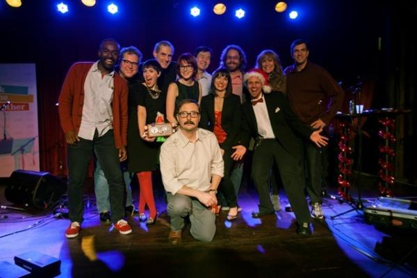 The spirit of the <em>Ask Me Another </em>crew cannot be stifled by the scrooge appearance of John Hodgman and his mustache (center)! From left to right up top, you're looking at John Asante, Eric Nuzum, Eleanor Kagan, John Chaneski, Jesse Baker, Art Chung, Ophira Eisenberg, Jonathan Coulton, Josh Rogosin, Lizz Wistead and A.J. Jacobs.