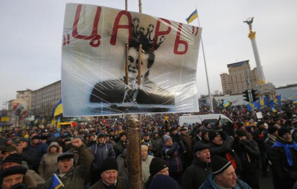 "Protesters hold a placard with a portrait of President Viktor Yanukovych and reading ""Tsar"" as they rally at the central Independence square in Kiev, Ukraine, on Tuesday, Dec. 3, 2013. (Sergei Grits/AP)"