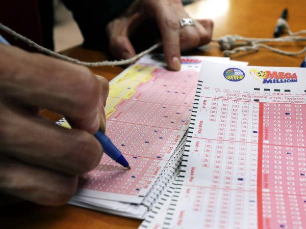 A woman picks her Mega Millions lottery numbers at a shop in New York's Penn Station on Tuesday. The Mega Millions jackpot soared to $636 million on Monday, still short of the $656 million U.S. record set in a March 2012 drawing.