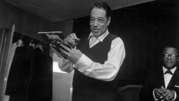Duke Ellington signs his biography in London in 1958, with Billy Strayhorn in the background. Ellington and Strayhorn collaborated to create 1960's <em>The Nutcracker Suite</em>.