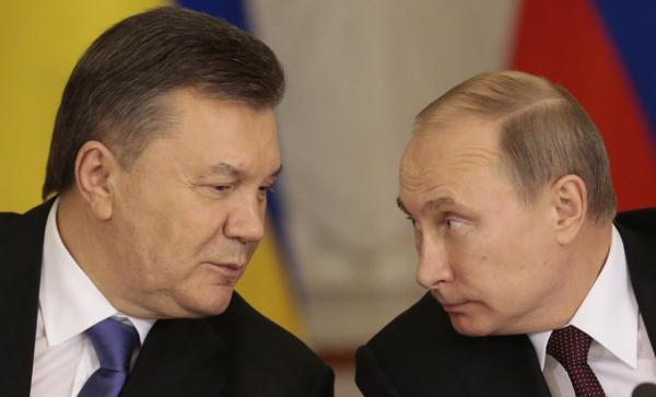 Russian President Vladimir Putin, right, and his Ukrainian counterpart Viktor Yanukovych chat during a news conference after their talks in Moscow on Tuesday, Dec. 17, 2013. (AP Photo/Ivan Sekretarev)
