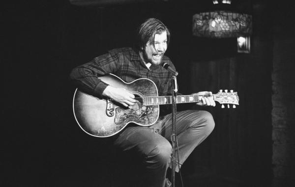 Armed with guitar, mike and enthusiasm, folk singer Dave Van Ronk performs at the Gaslight coffee house in New York's Greenwich Village on Nov. 8, 1963. (AP)