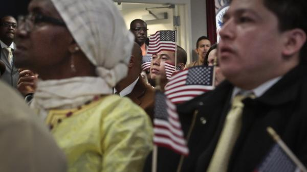 Immigrants hold miniature U.S. flags as they listen to a video broadcast from President Obama during a naturalization ceremony in New York City.