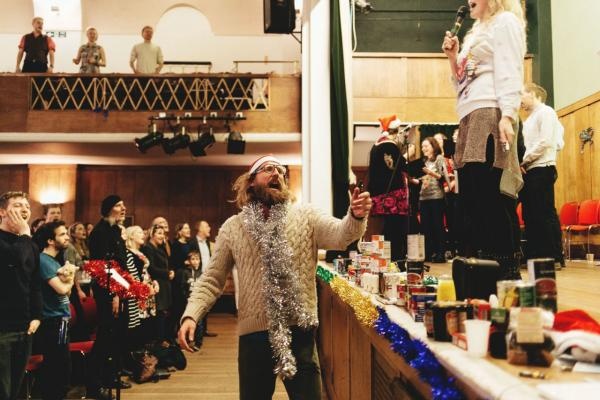 "Sanderson Jones, co-founder of Sunday Assembly, sings along at a ""Mythmas"" celebration in London. (Jack Davolio)"