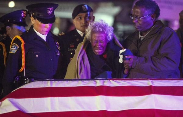 Clara Gantt, the 94-year-old widow of U.S. Army Sgt. Joseph Gantt, weeps in front of her husband's casket after it was lowered from the plane.
