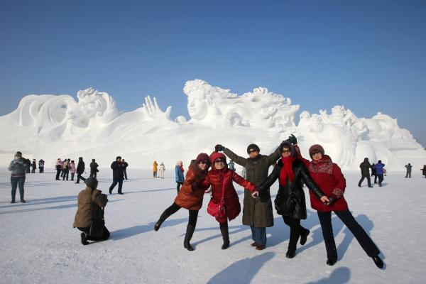 People pose beside a large snow sculpture at the 26th Harbin International Snow Sculpture Art Expo in Sun Island Park on Sunday in Harbin, China.
