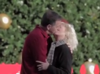 A couple kisses under a drone mistletoe.