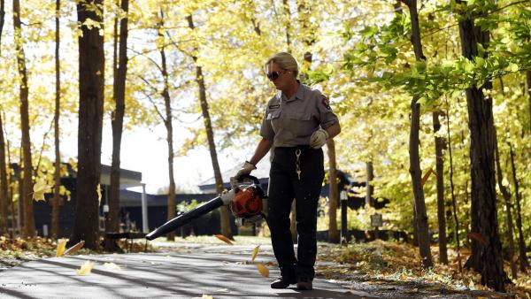 Cindy VanDerwerker, a maintenance worker at Saratoga National Historical Park, clears leaves from a walkway on Oct. 17 in Stillwater, N.Y.