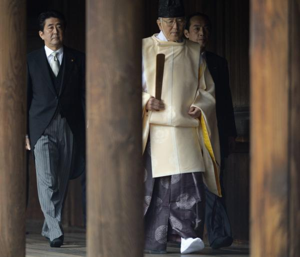 Japanese Prime Minister Shinzo Abe, left, follows a Shinto priest during his visit to the Yasukuni shrine in Tokyo on Thursday.