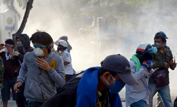 Thai anti-government protesters run from tear gas during a rally at a stadium to register party-list candidates in Bangkok. (AFP/Getty Images)