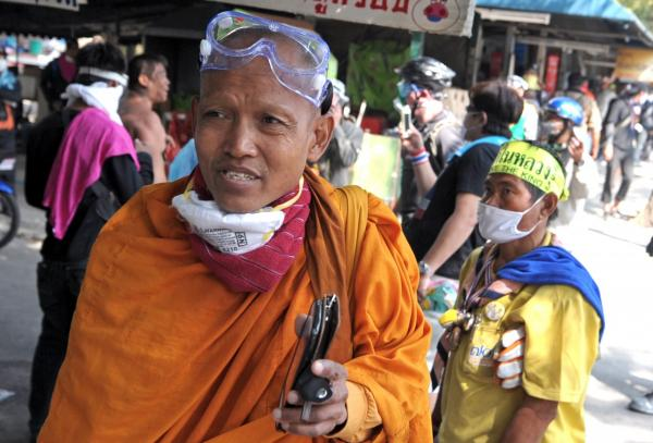 Thai buddhist monk wears a face mask after police gas as violence broke out at a protest against upcoming elections. (AFP/Getty Images)