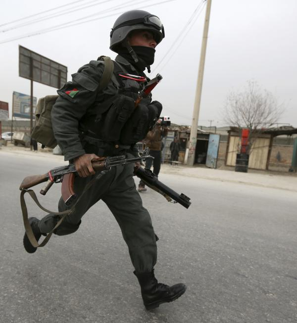 An Afghan security officer runs toward the scene of Friday's bombing in Kabul. Three NATO personnel were killed and at least six Afghan civilians were wounded.