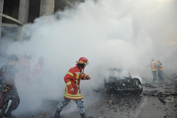 Lebanese security forces and firefighters inspect the scene of a car bomb explosion that rocked central Beirut on Friday.