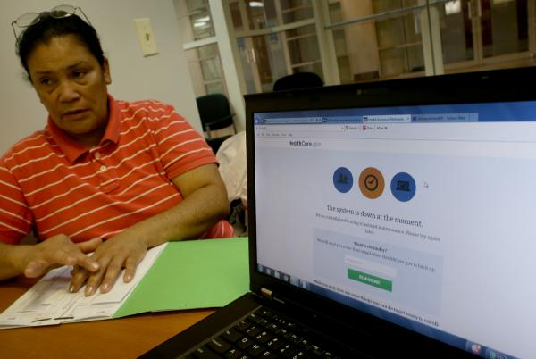 Alicia Martinez tries to sign up for a health care plan at a Miami Enrollment Assistance Center on Dec. 20, in Miami, Fla.