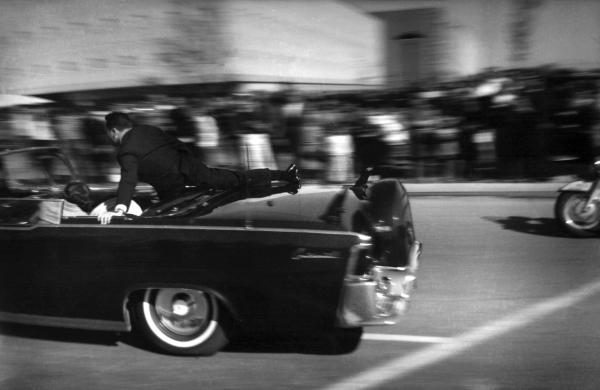 The limousine carrying mortally-wounded President John F. Kennedy races toward Parkland Hospital in Dallas just seconds after he was shot.