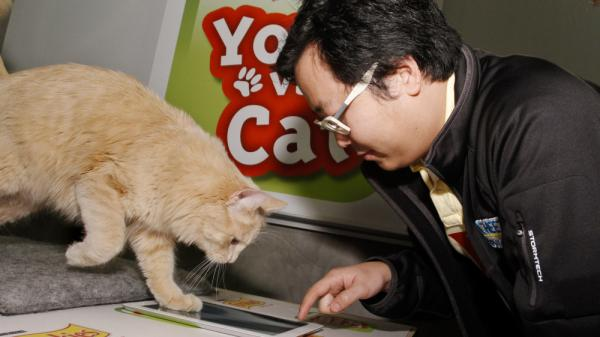 """In this photograph taken by AP images for Friskies, Ben Huh, of I Can Haz Cheezburger, challenges topcat gamer Buddy to a match of Friskies """"You vs. Cat"""" during the SXSW Interactive Festival on Sunday, Mar. 11, 2012."""