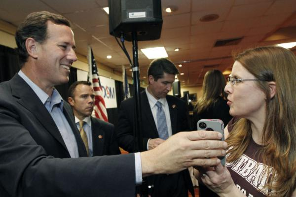 Rick Santorum takes the phone to speak to a supporter's husband, who couldn't attend a Shreveport, La., rally, on Friday.
