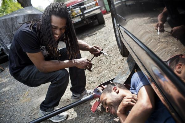 "Nicholas (left) laughs with his childhood friend Corey Buford while they work on Nicholas' car. Nicholas has briefly abandoned his music aspirations and is close to getting a job with Comcast to install cable. ""The money is more important,"" Nicholas says. ""I need something that I can contribute [to the household] with."""