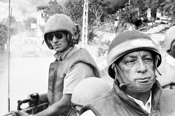 Sharon (foreground) rides an armored personnel carrier on a tour of Israeli units advancing to the outskirts of Beirut, Lebanon, on June 15, 1982, during the Israeli occupation.