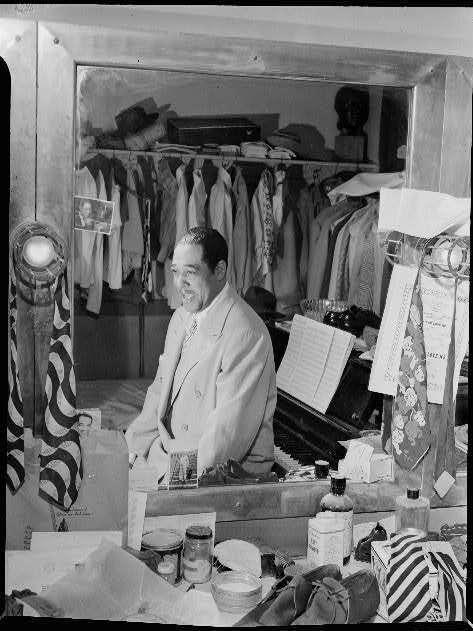 "Duke Ellington, amid ""his 20 suits, 15 shirts, suede shoes and his ever present piano"" in his dressing room at the Paramount Theater in New York in September 1946."
