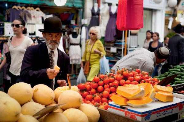 A shopper chooses a melon from a market stall in Jerusalem.