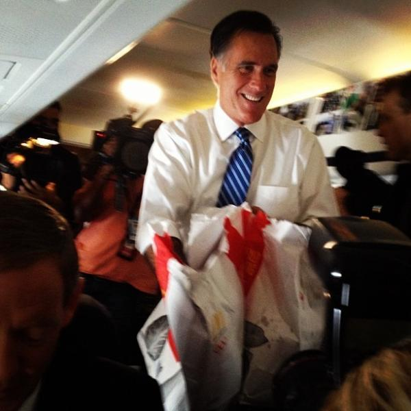 "Ari Shapiro explained what was going on when he took this photo of Mitt Romney handing out McDonald's hamburgers to members of the press during a flight: ""Romney: 'Quarter-pounder?' Press: 'Can you tell us more about your plans for Libya?"""