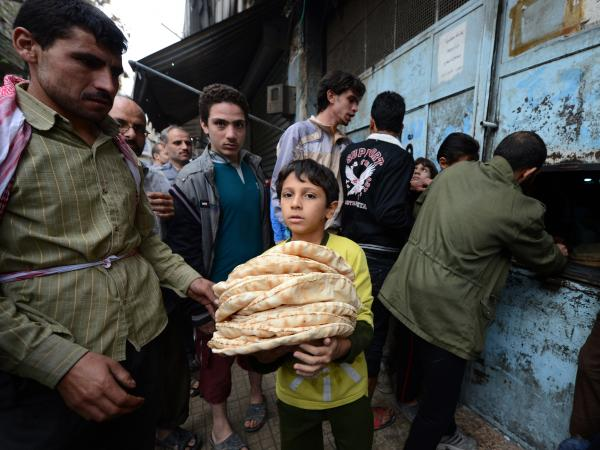 A Syrian boy carries a pile of bread as people crowd outside a bakery in the Salaheddin district of Aleppo, on Oct. 25, 2012.
