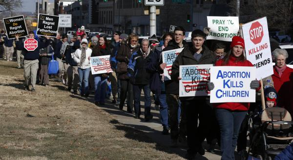Abortion opponents march to a rally at the Kansas Statehouse in Topeka, Kan., on the 40th anniversary of <em>Roe v. Wade.</em> Kansas is among several states that have enacted new restrictions on abortion in recent years.
