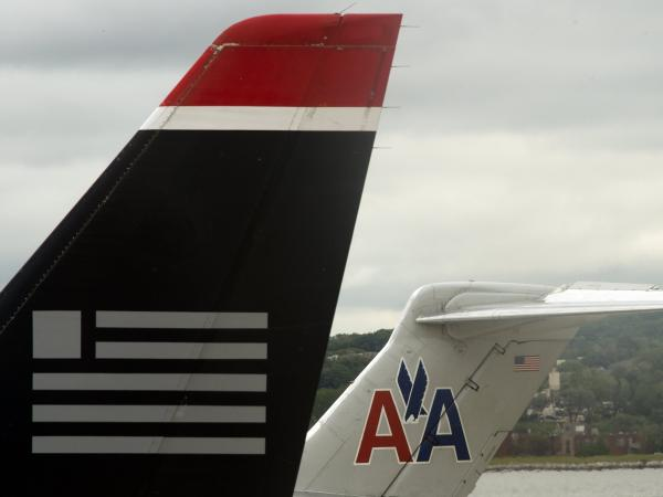 A US Airways jet rests on the tarmac near an American Airlines plane at Ronald Reagan Washington National Airport in Arlington, Virginia.