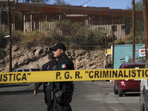 An investigator inspects a crime scene where a 16-year-old was shot. At least one U.S. Border Patrol agent shot into Mexico after rocks were thrown at him, hitting the teen.