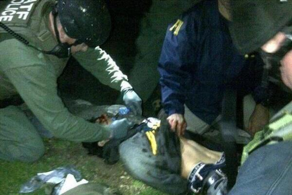 Tsarnaev, 19, is searched by law enforcement officers Friday.