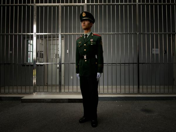 A paramilitary guard stands before the bars of a main gate to a detention center during a government guided tour in Beijing last year.