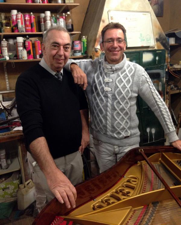 Michel Labord (left) technical director of the Colmann piano company, restores a Pleyel piano in his workshop with company founder Olivier Colin.