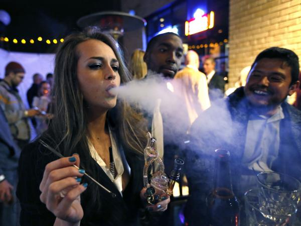 Partygoers smoke marijuana during a Prohibition-era themed New Year's Eve party celebrating the start of retail pot sales, at a bar in Denver, late Tuesday Dec. 31, 2013.