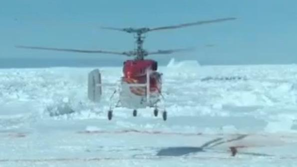 Help arrives: an image from video taken as a helicopter landed Thursday on an ice floe in the Antarctic. The copter then carried passengers from a stranded ship to another vessel waiting nearby in open waters.