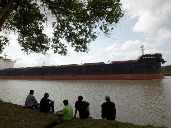 Men sit by the side of the Panama Canal as a ship sails past in Gamboa near Panama City, last month. The expansion project is aimed at accommodating the world's largest container ships.