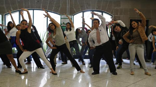 Government workers exercise at their office in Mexico City, August 2013. To counter the obesity epidemic, the city requires all government employees to do at least 20 minutes of exercise each day.