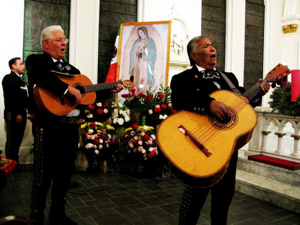 Jess Escalante (right), the 70-year-old founder of Mariachi Norteno, plays his guitarrón in a recent Mass for Our Lady of Guadalupe inside St. Joseph Catholic Church in Houston. He's joined by Jose Martinez.