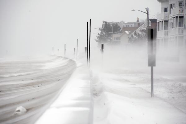 Winds whip snow from the beach across Winthrop Shore Drive in Winthrop, Mass.