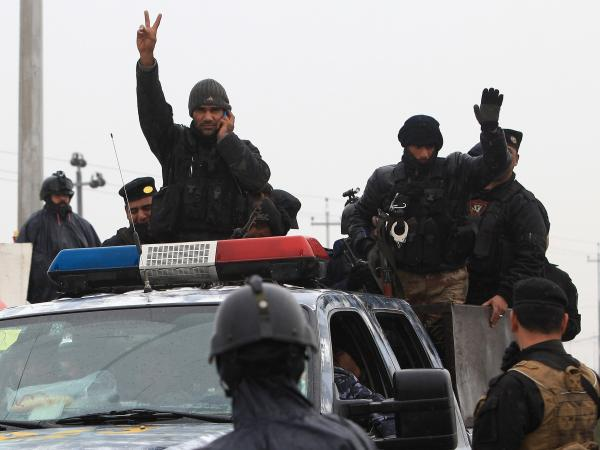 An Iraqi riot police officer flashes the V-sign as his unit returns to its headquarters from clashes with al-Qaida fighters in Basra, Iraq's second-largest city, in the restive Anbar Province.