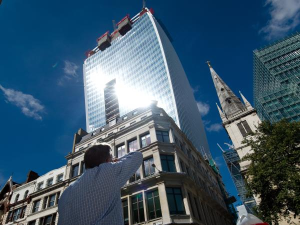 "A man reacts to a shaft of intense sunlight reflected from the glass windows of the new ""Walkie Talkie,"" or ""Walkie Scorchie,"" tower in central London on Aug. 30, 2013."