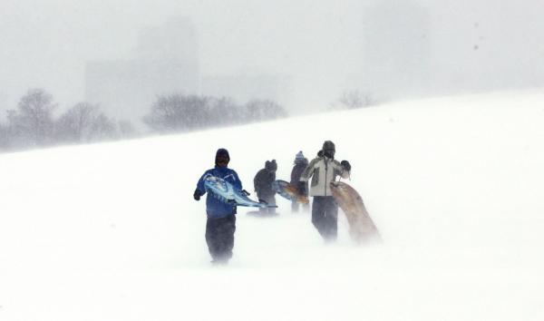 People carry sleds at Montrose Beach Park in Chicago on Sunday, Jan. 5, 2014. (Nam Y. Huh/AP)