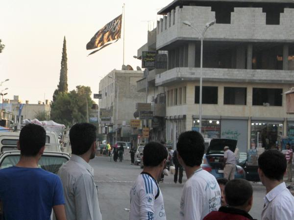 Men look at a jihadist flag flying over Raqqa on Sept. 28, 2013.