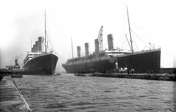 Olympic (left) returning to Belfast for repairs in March 1912, and Titanic (right). This was the last time the two sister ships would be seen together. (Robert John Welch/Wikimedia Commons)