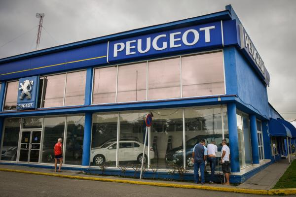 Cubans peer into the windows of a car dealer in Havana on Jan. 3. Cubans were astonished by a $250,000 Peugeot family sedan and other prices when the government lifted its 50-year restrictions on new and used car sales.